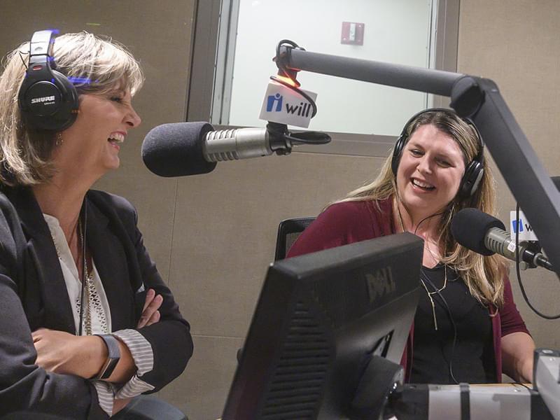 two women sit in a radio studio talking in front of microphones