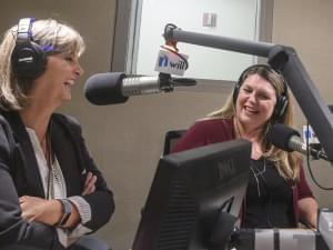 two women sit in a radio studio talking in front of microphones