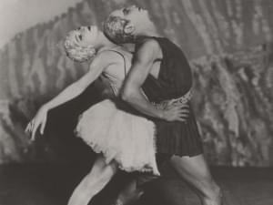 Two dancers perform on stage.