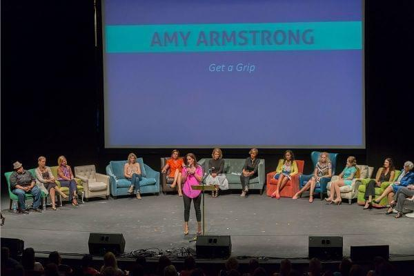 Amy Armstrong speaking on a stage with women listening to her in the background