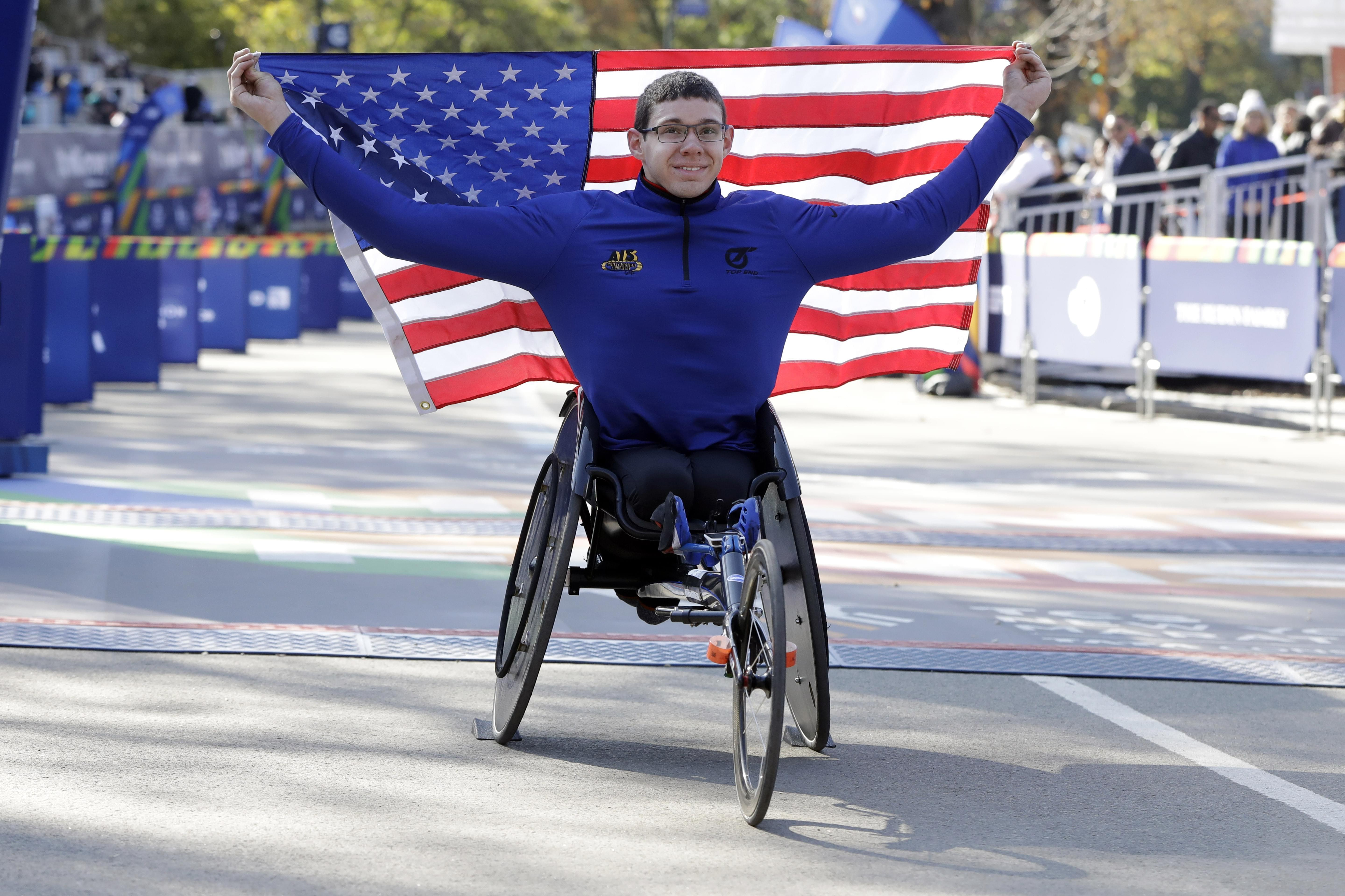 Daniel Romanchuk poses and American flag after winning the men's wheelchair division of the New York City Marathon.