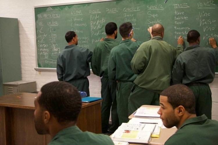 Men in prison stand in front of a black board.