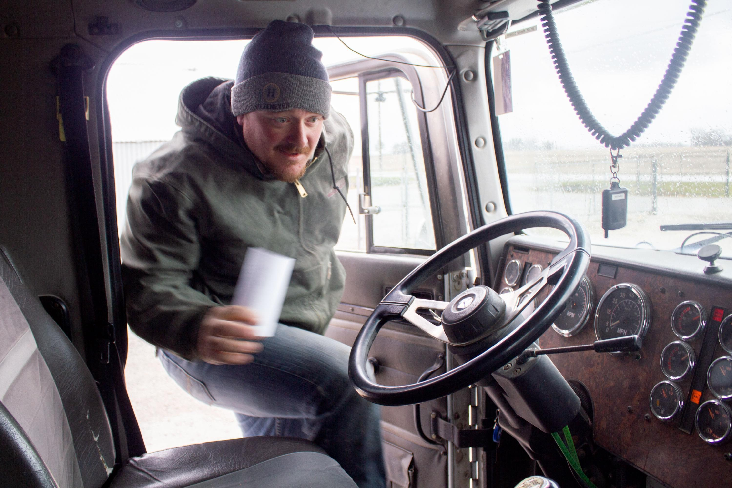 Central Iowa farmer Corey Hillebo climbs into the cab of his semi after picking up the receipt for corn he delivered to a grain elevator.