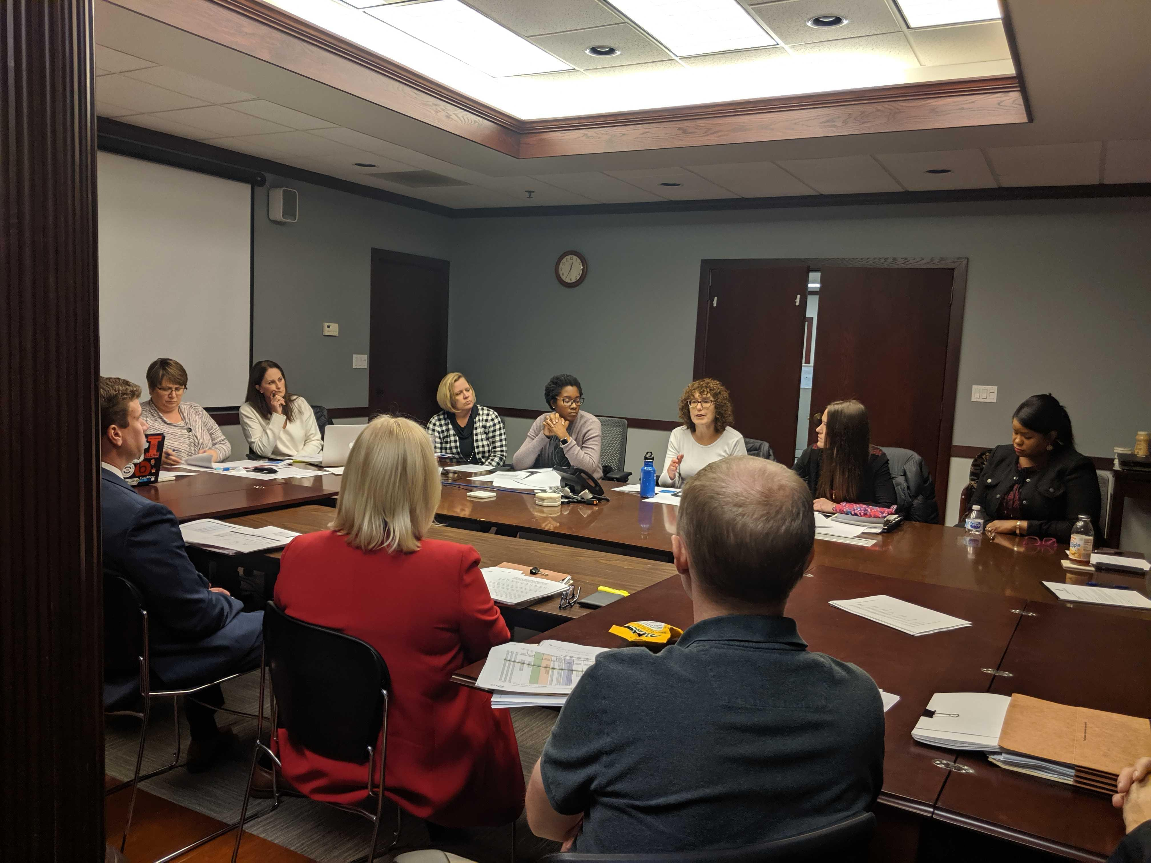 Champaign Unit 4 School Board members and other officials seated around a table in a conference room at one of the district's offices.