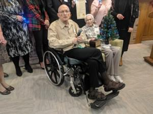 University of Illinois Professor Emeritus Nick Holonyak Jr. and his wife Kay seated with a fiber-optic Christmas tree in front of people standing behind them.