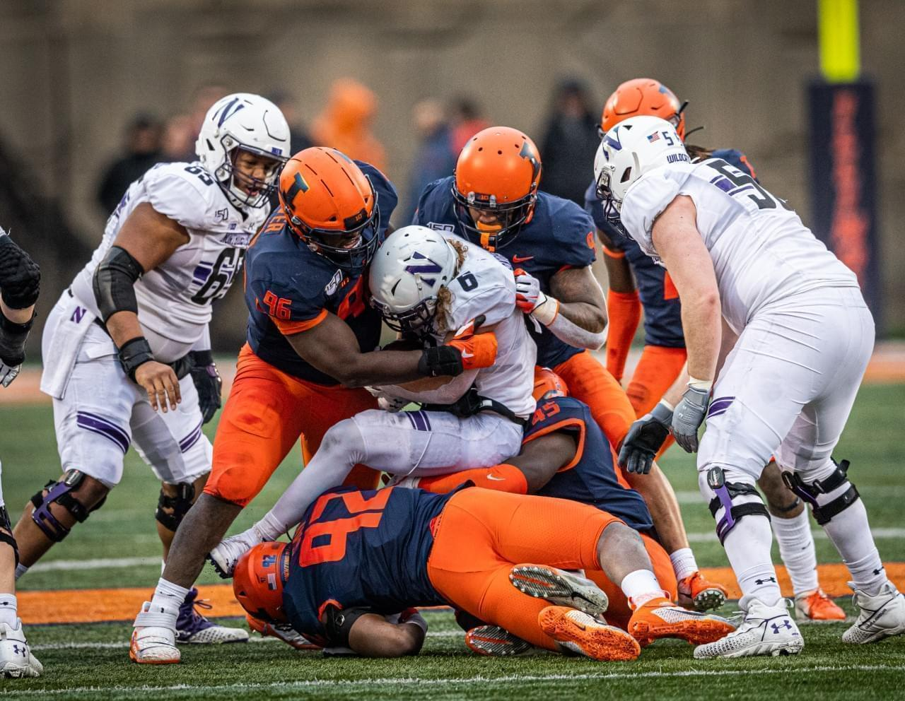 Illinois defenders bring down Northwestern running back Drake Anderson Saturday at Memorial Stadium in Champaign.