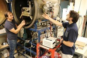 Aerospace engineering graduate students work with the vacuum chamber in Talbot Laboratory on the University of Illinois campus.