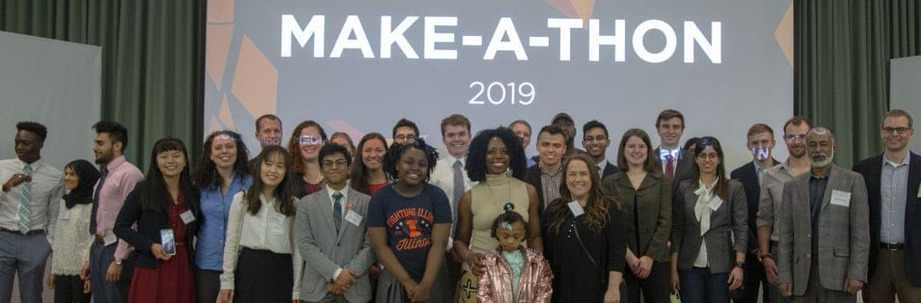 Winners of the first Health Make-A-Thon hosted by the Carle Illinois College of Medicine at the University of Illinois pose with U of I staff. Standing in a row in front a  projector screen.