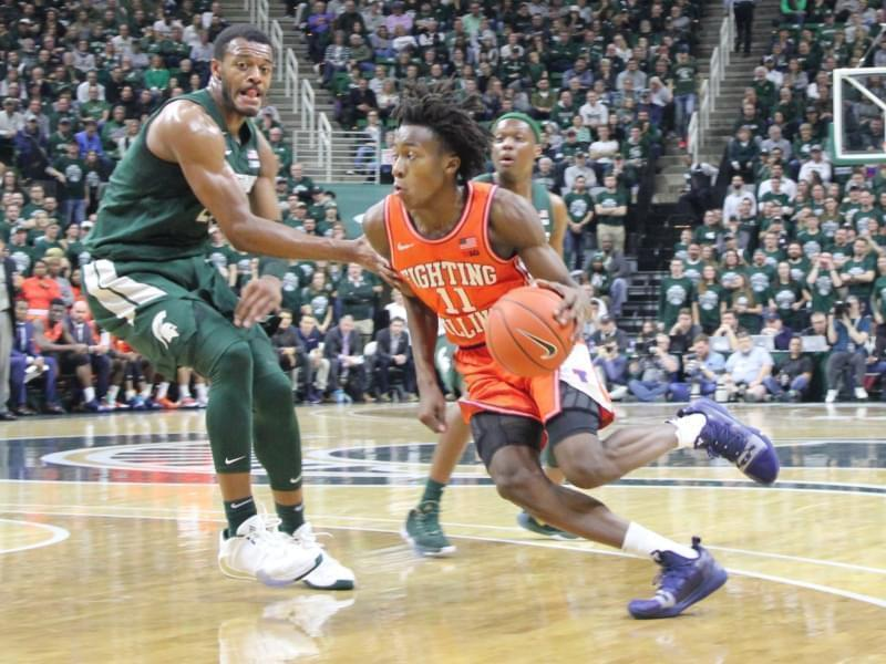 Illini guard Ayo Dosunmu drives spast Spartan defenders.
