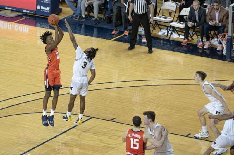 Ayo Dosunmu hits the game-winning shot over Michigan's Zavier Simpson in a 64-62 win on Saturday in Ann Arbor.