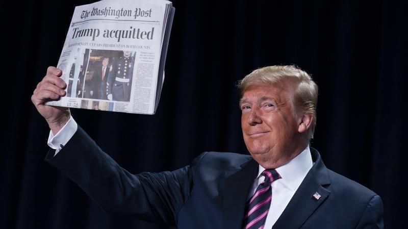 "President Trump holds up Thursday's Washington Post with the headline ""Trump acquitted."""
