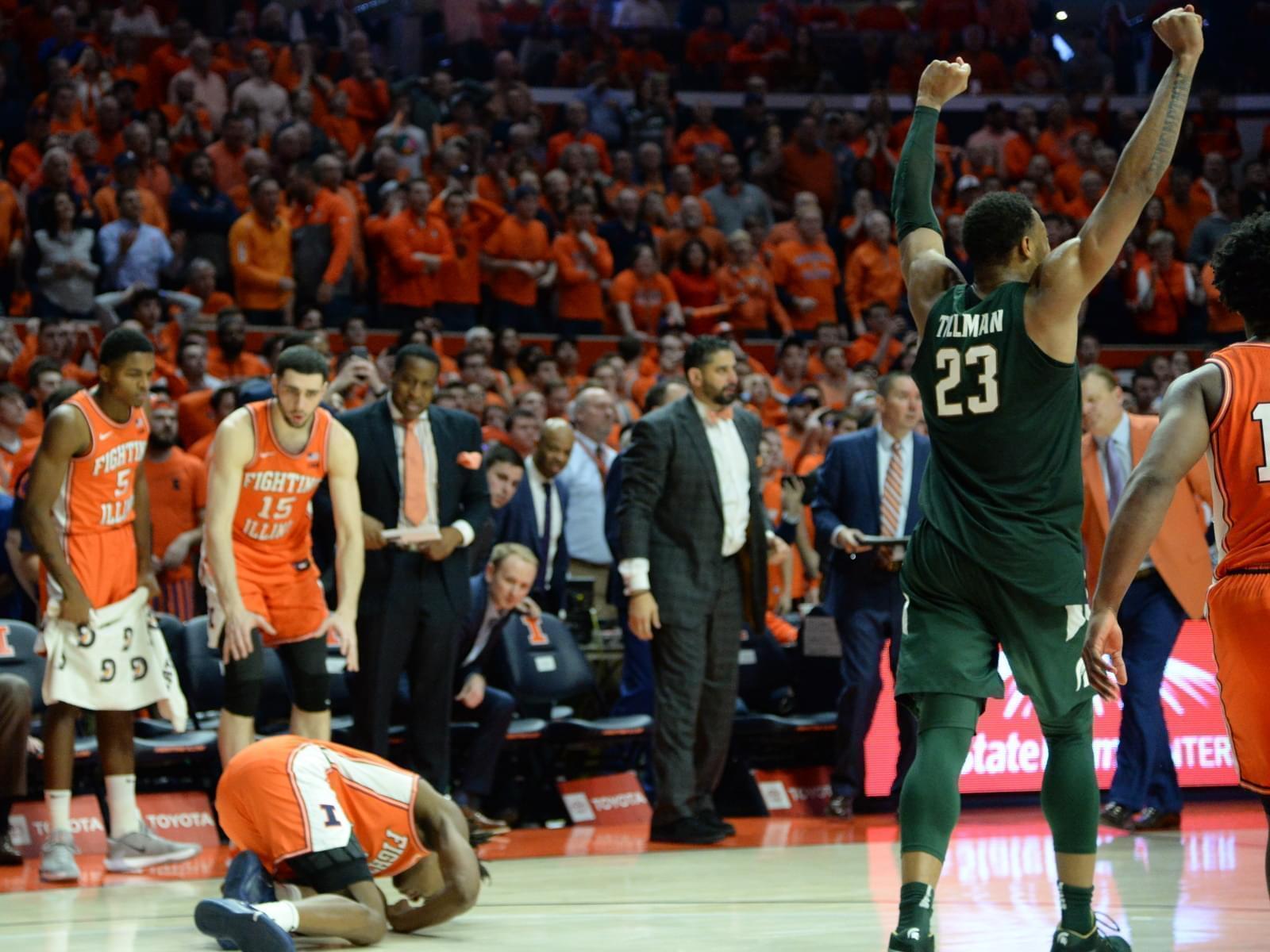 Michigan State's Xavier Tillman celebrates while Illinois' Ayo Dosunmu writhes in pain.