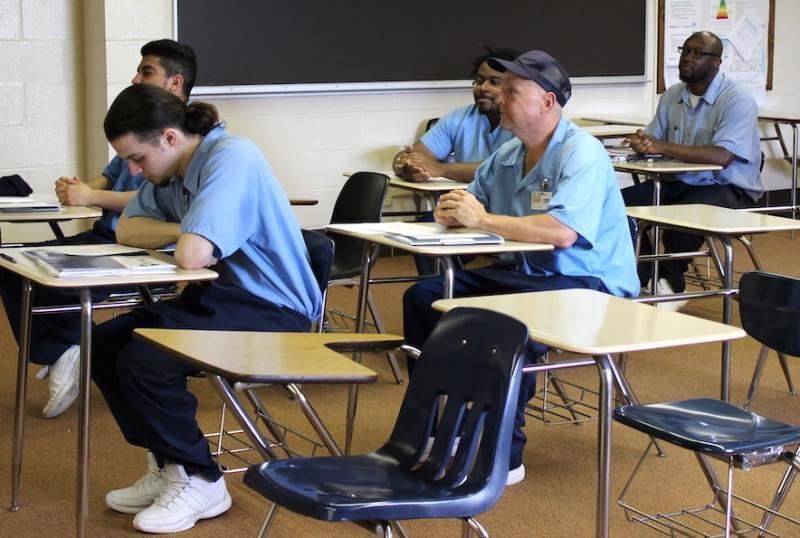 Incarcerated men sit at classroom desks inside a classroom at an Illinois prison