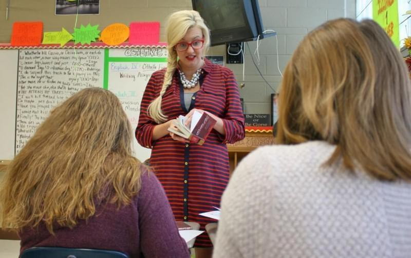 Lindsey Jensen standing in front of two seated students in her classroom