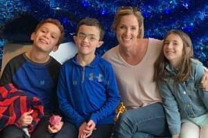 Lauren Kamnik and her three children pose for a photo seated in front of a blue background