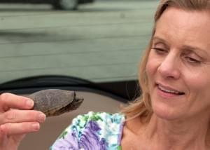 Sandy Mason holds up the turtle she rescued.