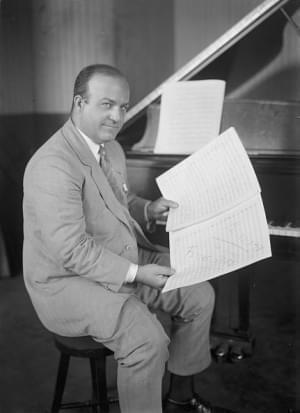 Ferde Grofe posing by piano with sheet music.