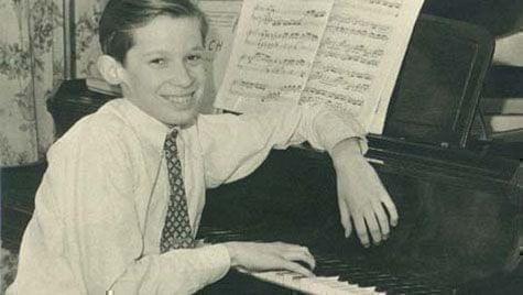 Young boy sits at piano smiling at the camera