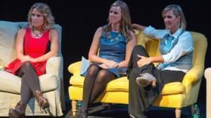 one woman sits on a couch and two other women sit on a loveseat
