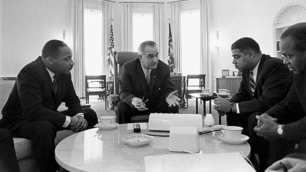 Four men sit around a table in the oval office talking