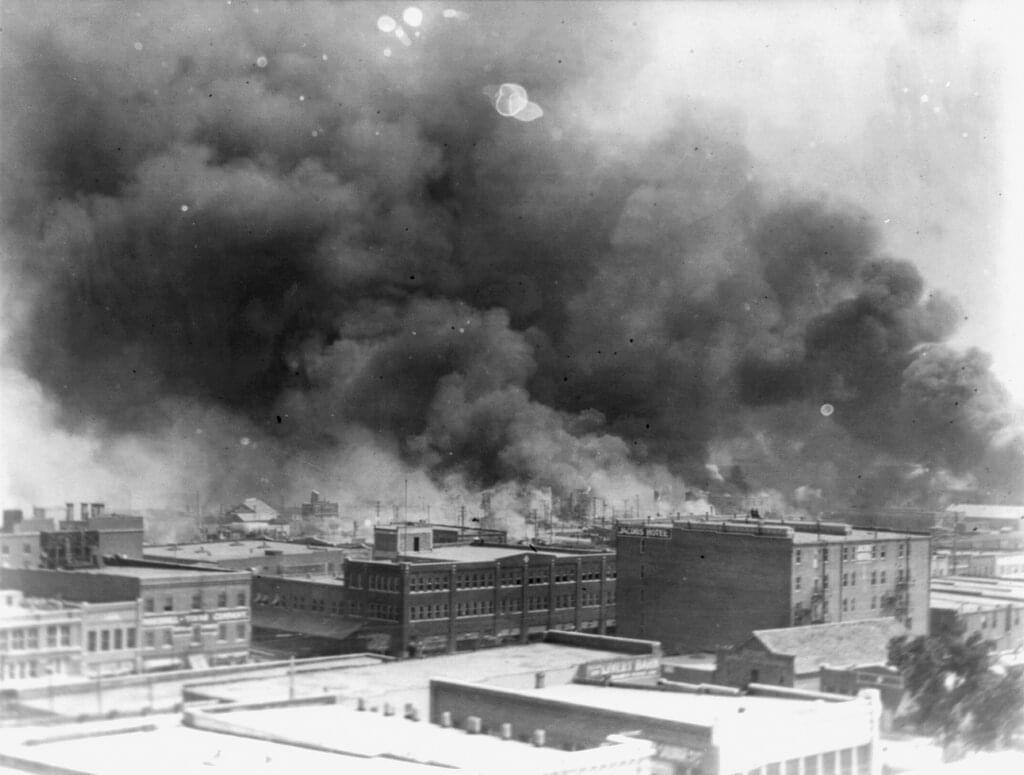 In this 1921 image provided by the Library of Congress, smoke billows over Tulsa, Okla. For decades, when it was discussed at all, the killing of hundreds of people in a prosperous black business district in 1921 was referred to as the Tulsa race riot.