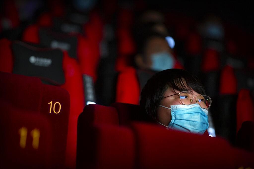 People wearing face masks to protect against the coronavirus watch a film at a movie theater in Beijing, Friday, July 24, 2020. Beijing partially reopened movie theaters as the threat from the coronavirus continues to recede in China's capital.