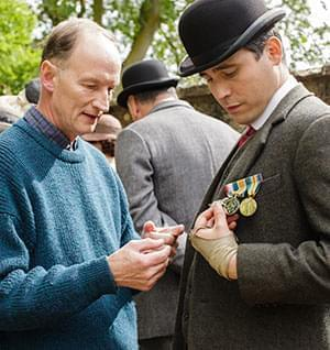 Alastair Bruce describes Thomas' medals to actor Rob James-Collier.