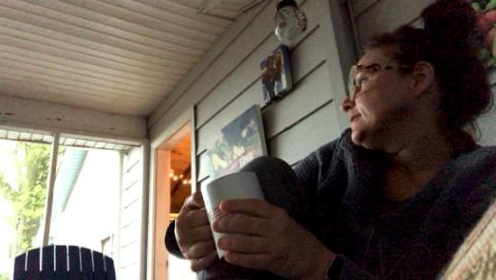 Angie Rouley sits on her front porch during a thunderstorm.