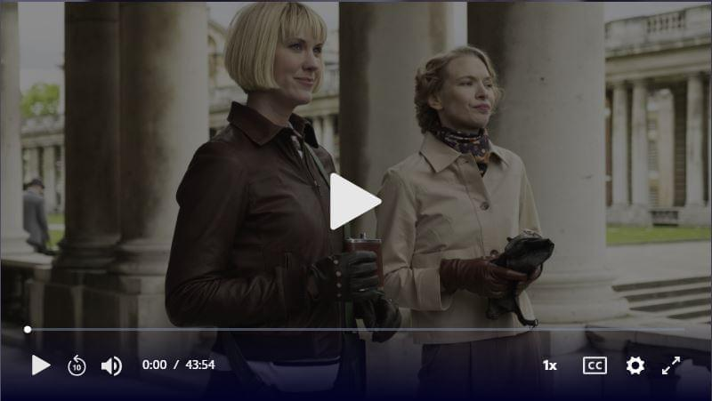 Two women stand outside looking ahead. Click to play video.