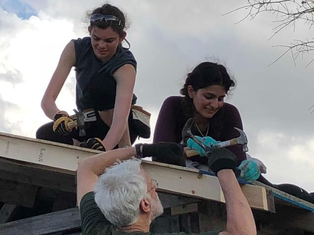 Students hammering shingles on the roof of a house