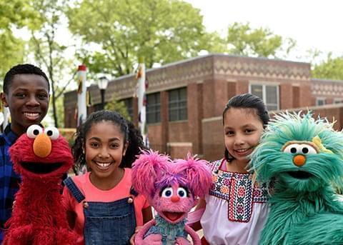 Kids smiling with Sesame Street characters