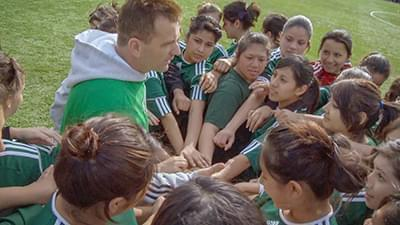 a male coach and a number of young girls in a sports huddle