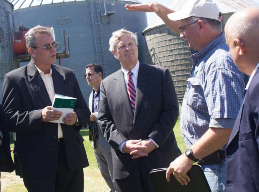 U.S. Secretary of Agriculture Tom Vilsack (center) and Cuban Agriculture Minister Gustavo Rodriguez Rollero (left) listen to Iowa farmer Aaron Lehman during a tour of Lehman's farm in 2016.